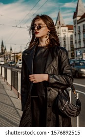 Outdoor fashion portrait of young elegant brunette woman wearing trendy sunglasses, long black leather trench coat, holding small hobo bag, handbag, posing in street of European city