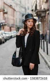 Outdoor fashion portrait of young elegant confident model, woman wearing trendy faux leather bucket hat, black suit, holding stylish hobo bag, handbag, posing in street of European city