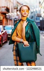 Outdoor fashion portrait of young fashionable girl wearing autumn outfit: orange glasses, turtleneck, checked culottes, leather jacket, holding green blue handbag, posing in street of european city