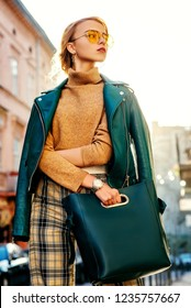 Outdoor fashion portrait of young fashionable girl wearing autumn outfit: yellow glasses, cashmere turtleneck, checkered trousers, leather jacket, holding green blue handbag, posing in street