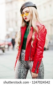 Outdoor fashion portrait of young fashionable lady wearing red biker jacket, stylish yellow sunglasses, leather beret, green turtleneck, trendy snake skin print trousers, posing in street of city