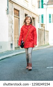Outdoor fashion portrait of young girl walking down the street, wearing bright red stylish coat