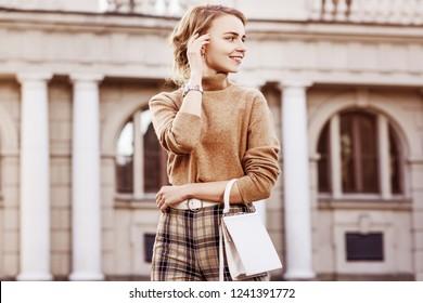 Outdoor fashion portrait of young happy smiling lady wearing trendy beige turtleneck, high-waisted checkered trousers, wrist watch, belt, carrying small white bag, posing in street. Copy, empty space