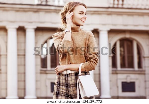 トレンディベージュのタートルネックの高いウェイト柄のベジュートルネックを着た若い幸せな女性のアウトドアファッションのポートレート、腕時計、ベルト、小さな白い袋を持ち、通りにポーズを入れている。コピー、空白