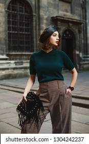 Outdoor fashion portrait of young lady wearing leather beret, green t-shirt, wrist watch, checkered trousers,  holding trendy black suede bag with fringe,  posing in street of European city