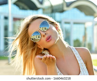 Outdoor fashion portrait of young pretty   blond woman in sunny day on street. Girl in sunglasses outdoor. Happy Fashion Woman in Sunglasses. Smiling Trendy Girl in Summer. Sends Air kiss