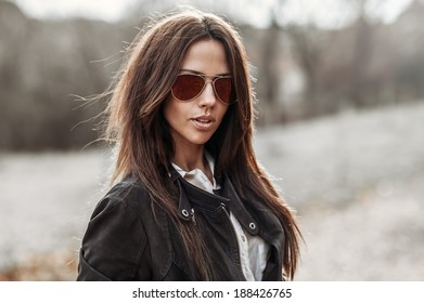 Outdoor fashion portrait of young pretty woman in sunglasses