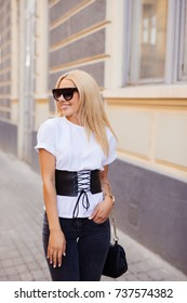 Outdoor fashion portrait of young pretty blond woman in sunny day on street. Girl in sunglasses outdoor. Happy Fashion Woman in Sunglasses. Smiling Trendy Girl in Summer.
