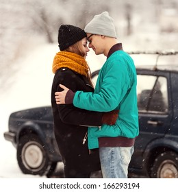 outdoor fashion portrait of young sensual couple in cold winter weather. love and kiss , car