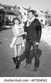 Outdoor fashion portrait of young sensual couple in cold winter weather. Love and kiss. Young man and woman in fashionable clothing in the winter in the city. Black and white photo.