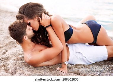 Outdoor fashion portrait of young sexy sensual couple lay on the beach.passion between two lovers.Love on the beach,tender kisses and touching passionate between two peoples.man and his girlfriend