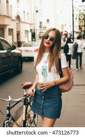 Outdoor fashion portrait of young stylish stunning woman, wearing hipster jeans skirt and elegant glamour bright t-shirt,red lips make up, posing at city cafe terrace, traveling clone, sunny day.ride
