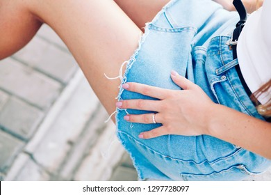 Outdoor Fashion street portrait of glamour petite girl, smart casual outfit, stylish hipster clothes. Outfit details of woman's jeans skirt perfect nails and manicure