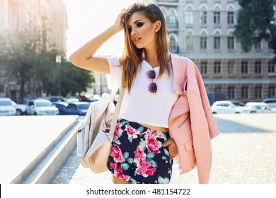 Outdoor fashion   street stile portrait of pretty   woman  in fall casual outfit  walking in city. Beautiful brunette girl or student enjoying  weekends.