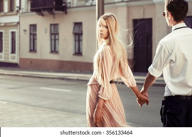 Outdoor fashion stunning sensual portrait of young couple in love walking on the street and having fun together