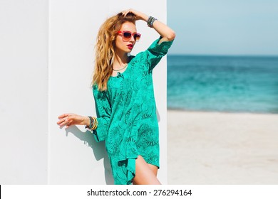 Outdoor fashion summer portrait of beautiful  slim tan woman with perfect bode in bright boho beach dress and cool  accessories , stylish sunglasses on the paradise tropical  breach.