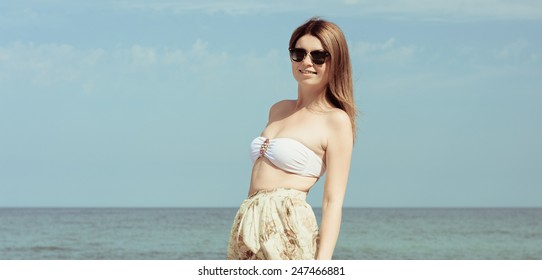 Outdoor fashion warm colors portrait of young sensual happy woman in skirt, bikini and sunglasses. model posing