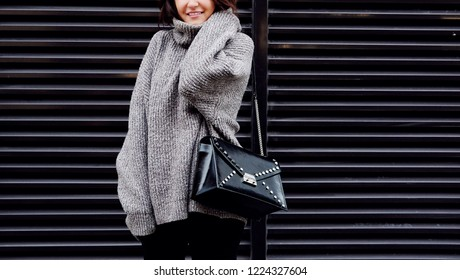 Outdoor fashion young stylish woman with trendy fall outfit, gray sweater and leather black bag. Cold season. Warm clothes.
