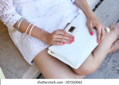 Outdoor fashion young woman hold white clutch with pink manicure
