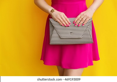 Outdoor fashionable girl in pink dress with striped handbag clutch near yellow wall . Stylish accessory