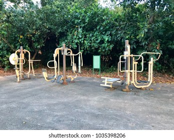 Outdoor fitness corner with exercise equipment in a park.