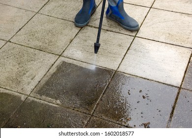 Outdoor floor cleaning with high pressure water jet. Man in rubber boots