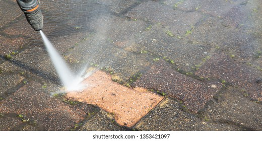 Outdoor floor worker cleaning with high pressure water jet