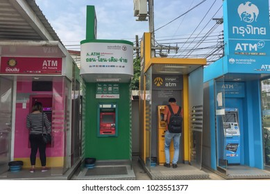 Outdoor four Thai ATM machines with few people doing businesses transactions in front of a local store in Loei, Thailand in February 4 2017.