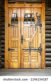 Outdoor front view of a naturally wood finished door entrance. Rustic traditional decorative pattern with iron fittings.