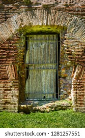 Outdoor front view of one old ancient weathered wooden entrance door and orange brick wall. Roman architecture.
