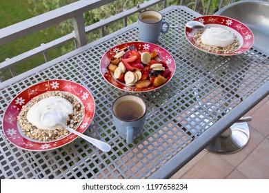 Outdoor fruit breakfast. Oat flakes with plain yogurt.