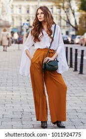 Outdoor full body fashion portrait of young beautiful woman wearing stylish yellow high-waisted wide-leg pants, white blouse, holding green leather bag. Model posing in street of european city