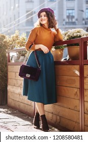 Outdoor full body fashion portrait of young beautiful woman wearing stylish  beret, orange turtleneck, midi green blue skirt, ankle boots, holding quilted purple bag, posing in street of european city