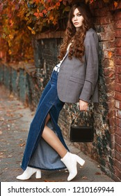 Outdoor full body fashion portrait of young beautiful fashionable woman wearing turtleneck, checked blazer, denim palazzo trousers, white ankle boots, holding small black bag, posing in autumn street