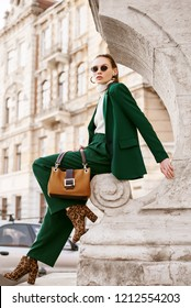 Outdoor full body fashion portrait of  fashionable woman wearing sunglasses, white turtleneck, green suit, blazer, trousers, leopard print boots, holding suede bag, posing in street of european city