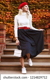 Outdoor full body fashion portrait of young beautiful girl wearing red beret, belt, white turtleneck, polka dot midi skirt, sneakers, wrist watch, holding small bag, posing in autumn street