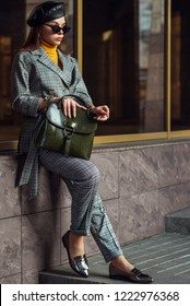 Outdoor full body fashion portrait of  elegant businesswoman, woman wearing glasses, beret, checked suite, blazer, trousers, loafers, holding leather handbag, posing in street of european city