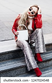 Outdoor full body fashion portrait of young fashionable lady wearing biker jacket, sunglasses, turtleneck, trendy snake skin print trousers, red boots, holding white bag, sitting on stairs, in street