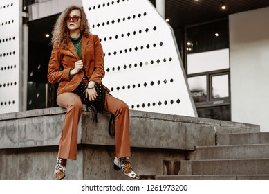 Outdoor full body fashion portrait of young confident woman wearing leopard print sunglasses, brown corduroy blazer, trousers, cowboy boots  holding suede bag with fringe, posing in street. Copy space