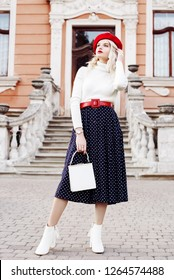 Outdoor full body fashion portrait of young beautiful girl wearing red beret, belt, turtleneck, polka dot midi skirt, white ankle boots, heels, holding small bag, posing in old european street
