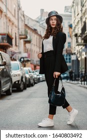 Outdoor full body fashion portrait of elegant luxury woman wearing faux leather bucket hat, black suit, white sneakers, holding hobo handbag, walking in street of European city