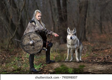 Outdoor full body portrait of furious northern warrior woman with blonde hair in a traditional clothes with fur collar, war makeup, shield and sword, with wolf, forest background