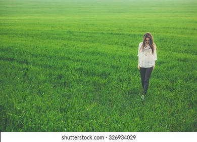 Outdoor full body portrait of sad lonely girl in green field. Young woman walking in meadow with copy space.