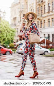 Outdoor full body portrait of yong beautiful happy smiling woman wearing stylish jumpsuit with floral print, hat, red shoes, holding straw bag. Model walking in street of european city