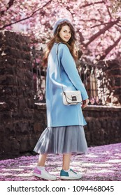 Outdoor full body portrait of young beautiful fashionable smiling girl walking in street. Model wearing trendy pastel blue coat, beret, midi skirt, sneakers, with white bag. Spring fashion concept