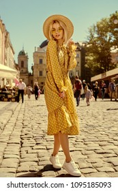 Outdoor full body portrait of young beautiful fashionable girl wearing trendy yellow color sunglasses, straw boater hat, polka dot dress posing in street of european city. Summer fashion concept