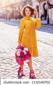 Outdoor full body portrait of young beautiful happy smiling girl wearing yellow polka dot dress, sandals, holding straw bag with peonies, walking in street of european city. Spring, summer fashion