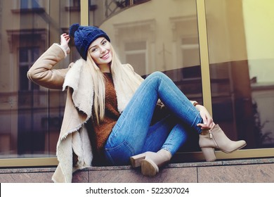 Outdoor full body portrait of young beautiful happy smiling girl posing on street. Model looking at camera. Lady wearing stylish winter clothes. Female fashion. Toned