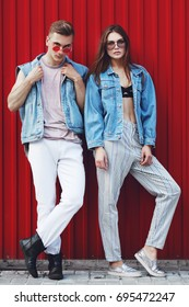 Outdoor full body portrait of young beautiful fashionable couple posing in street. Models wearing stylish denim clothes, trendy sunglasses. Red background. Fashion concept. City lifestyle