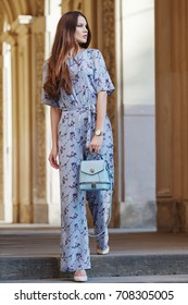 Outdoor full body portrait of young beautiful fashionable woman walking in street. Model wearing stylish jumpsuit with flower print, wrist watch, a lot of rings, holding light blue bag. Female fashion